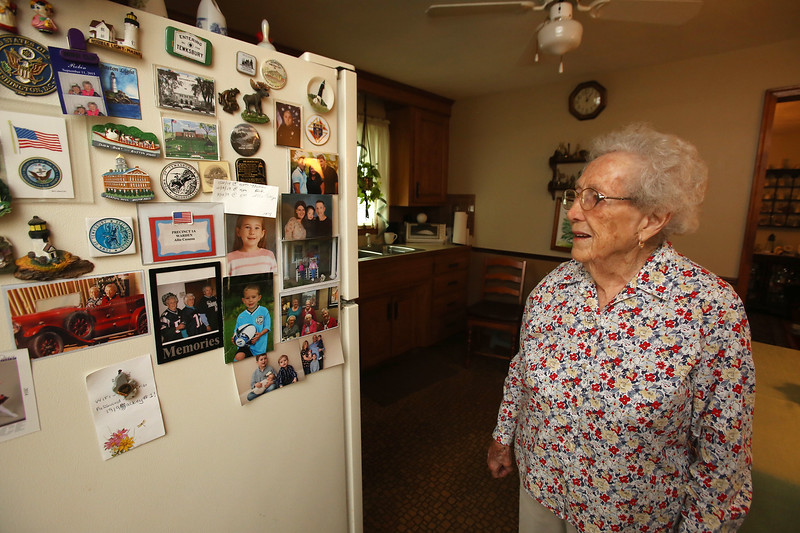Allie Casazza of Tewksbury recently celebrated her 100th birthday. In her kitchen, this is the overflow side of photos of her family including four daughters, 10 grandchildren, 16 great-grandchildren, and four great-great-grandchildren, and town of Tewksbury memorabilia. (SUN/Julia Malakie)
