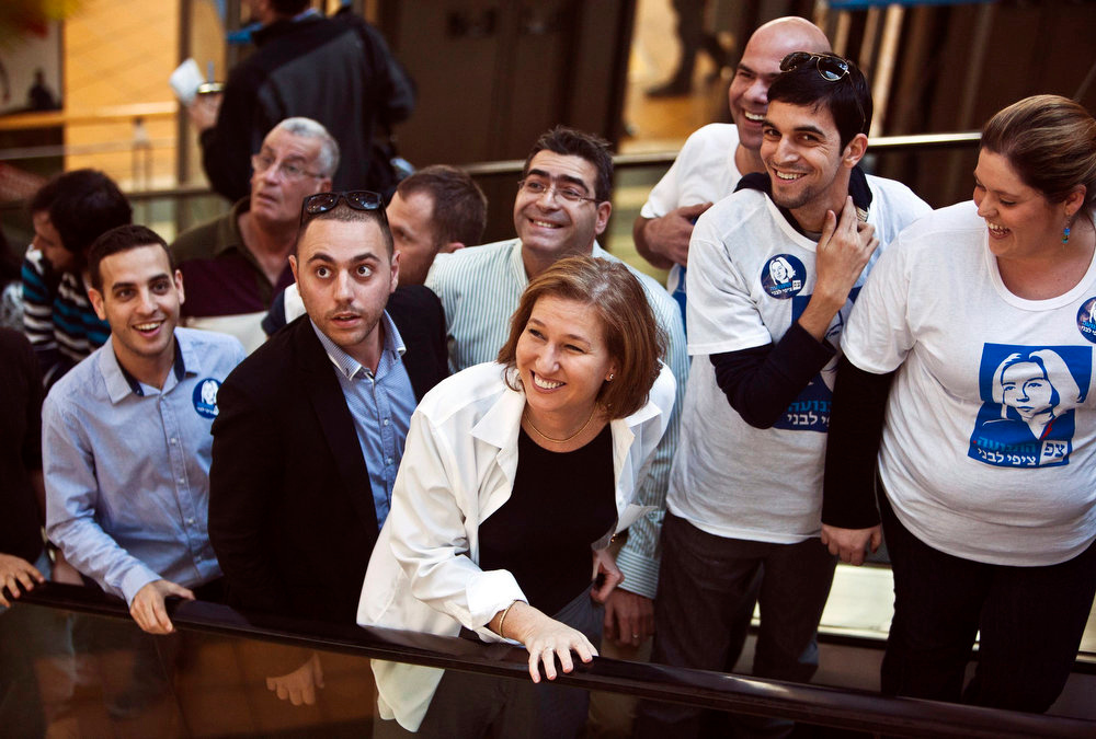 Description of . Hatnua party leader Tzipi Livni (C) smiles on a campaign stop at a mall in Tel Aviv ahead of Tuesday's parliamentary election January 21, 2013. The party was founded just two months ago by former foreign minister and ex-Kadima leader Livni as a centrist alternative to Israel's right-wing leadership.  REUTERS/Nir Elias