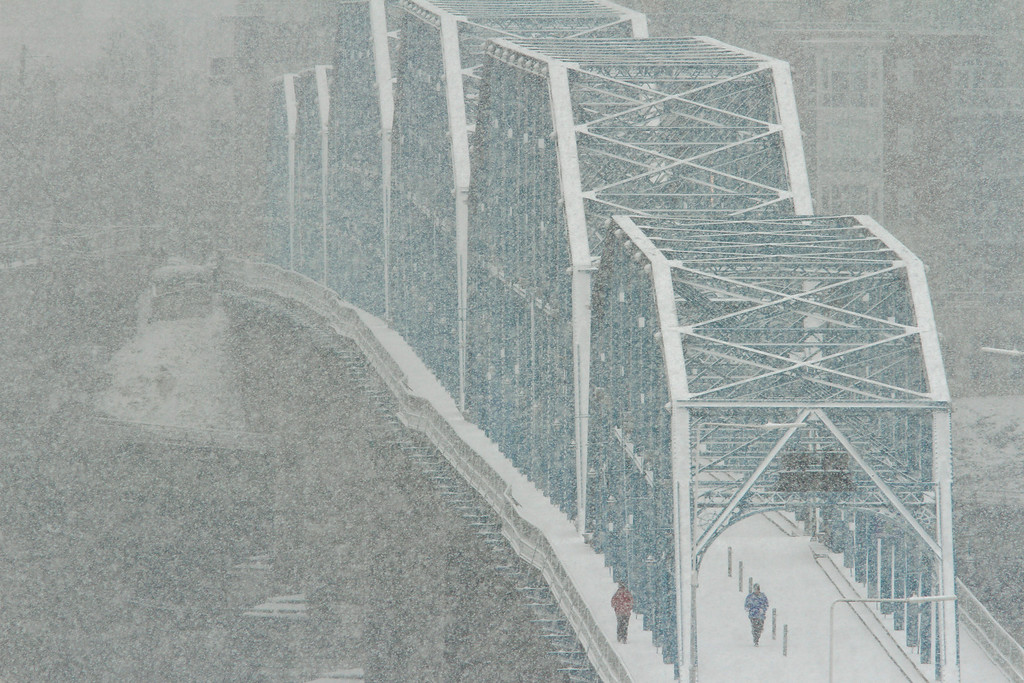 . Pedestrians walk across the Walnut Street Bridge as snow accumulates on Wednesday, Feb. 12, 2014 in Chattanooga, Tenn. The bridge is a pedestrian bridge that spans the Tennessee River. Slushy highways and streets were mostly desolate and ice encased trees and sent them crashing into power lines, knocking out electricity to a wide swath of the South as the winter-weary region was hit with its second winter storm in two weeks. (AP Photo/Chattanooga Times Free Press, Dan Henry)