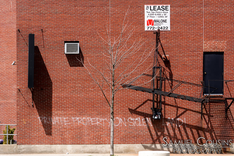 "Graffiti on the side of a building, that says ""Private Property on Stolen Land!"""