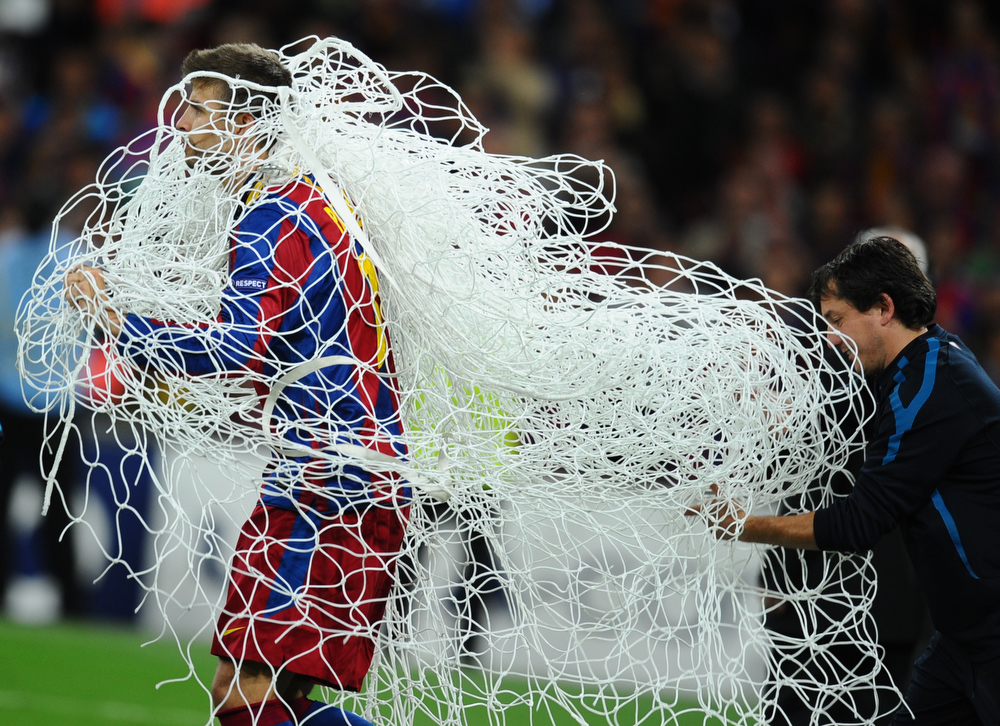 Description of . Barcelona's Spanish defender Gerard Pique runs with the goal's net as he celebrates at the end of the UEFA Champions League final football match FC Barcelona vs. Manchester United, on May 28, 2011 at Wembley stadium in London.Barcelona won 3 to 1. AFP PHOTO / LLUIS GENE