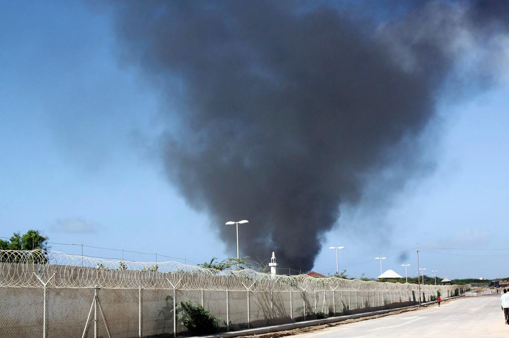 . Black smoke rises over the scene of a plane crash at the Mogadishu airport in Mogadishu, Somalia, Friday, Aug. 9, 2013.  (AP Photo/Farah Abdi Warsameh)