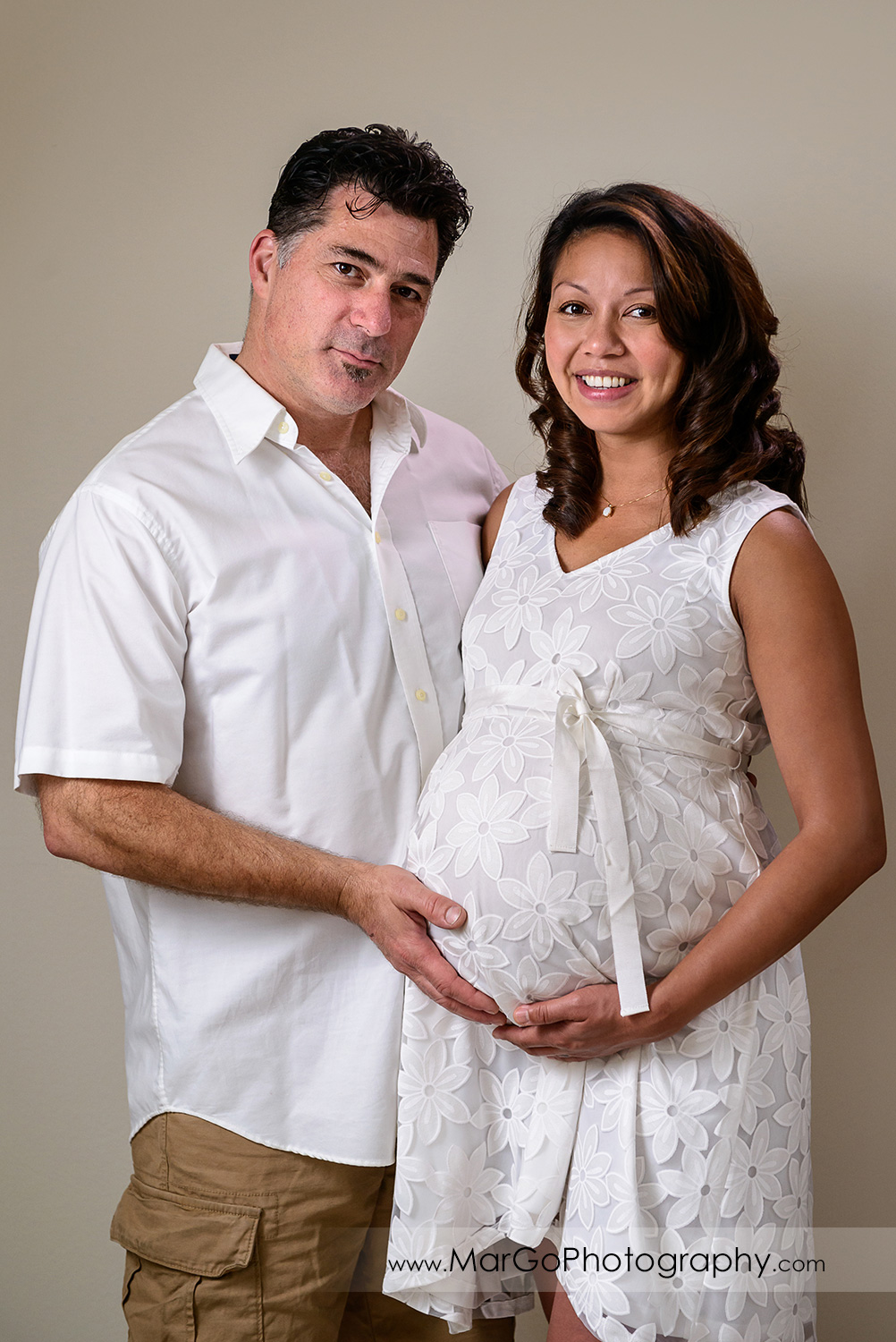 pregnant woman in white dress and man in white shirt facing each other and looking into camera during maternity session