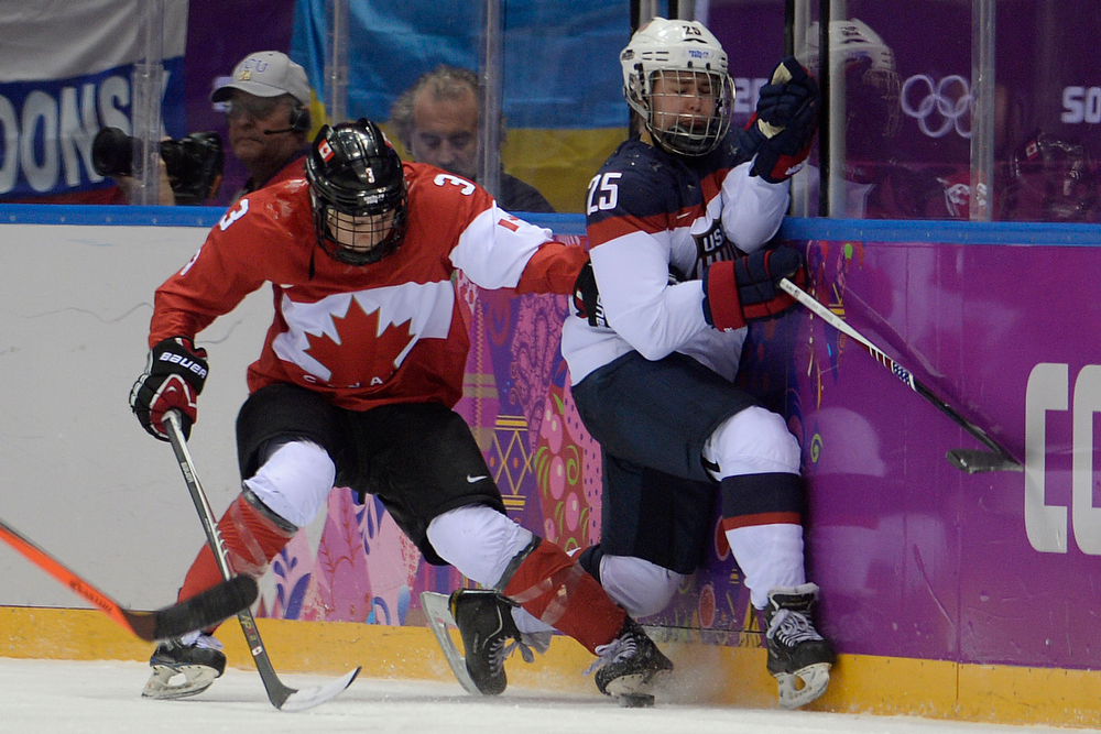 . Jocelyne Larocque (3) of the Canada checks Alex Carpenter (25) of the U.S.A. into the boards during the second period of the women\'s gold medal ice hockey game. Sochi 2014 Winter Olympics on Thursday, February 20, 2014 at Bolshoy Ice Arena. (Photo by AAron Ontiveroz/ The Denver Post)