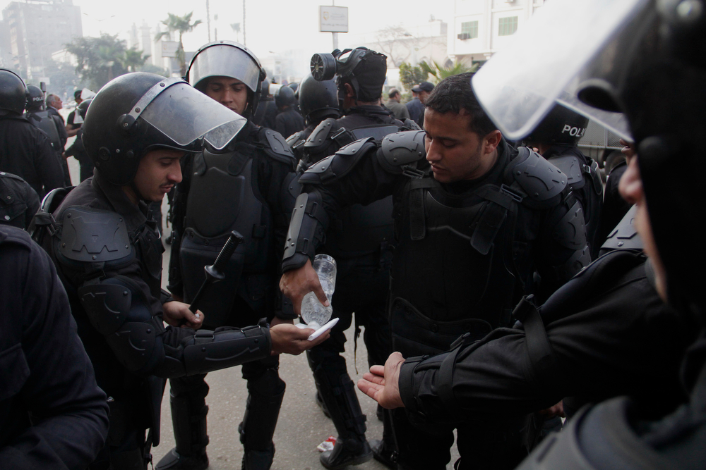 . One of the Egypt\'s security forces receive water from another during clashes with supporters of ousted President Mohammed Morsi in Cairo, Egypt, Friday, Jan. 17, 2014. Morsi supporters held sporadic protests against this week\'s constitutional referendum as authorities said there was a deadly clash. (AP Photo/Aly Hazzaa)