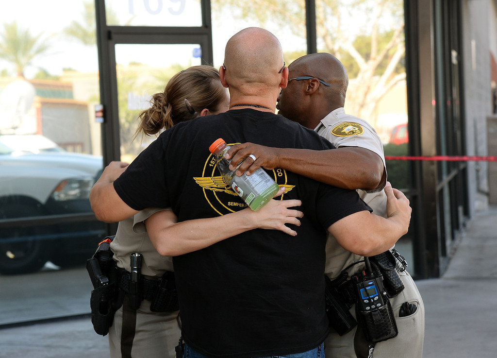 . Las Vegas Metropolitan Police Department officers embrace near a Wal-Mart on June 8, 2014 in Las Vegas, Nevada.   (Photo by Ethan Miller/Getty Images)