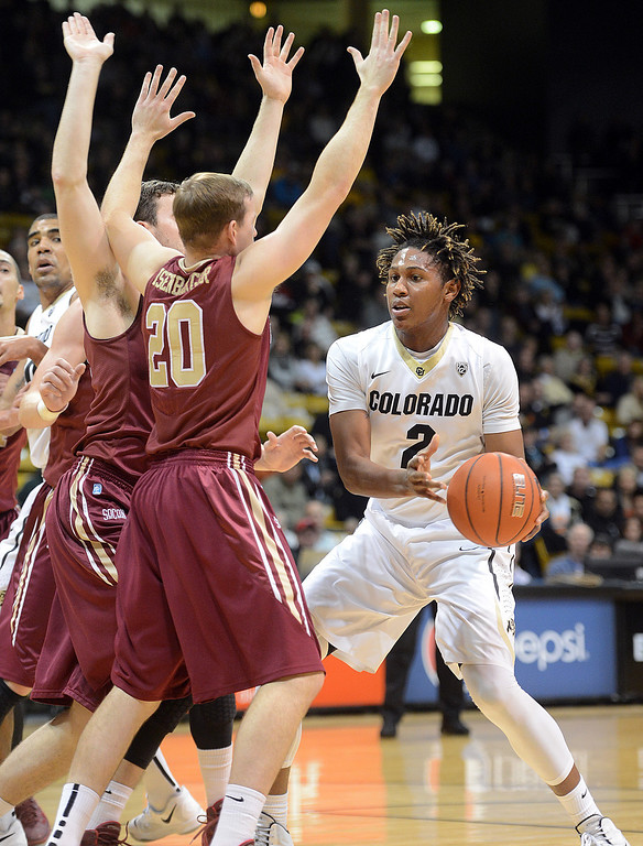 . Xavier Johnson, of CU, looks to pass around Jack Isenbarger of Elon during the first half of the December 13, 2013 game in Boulder. (Cliff Grassmick/Boulder Daily Camera)