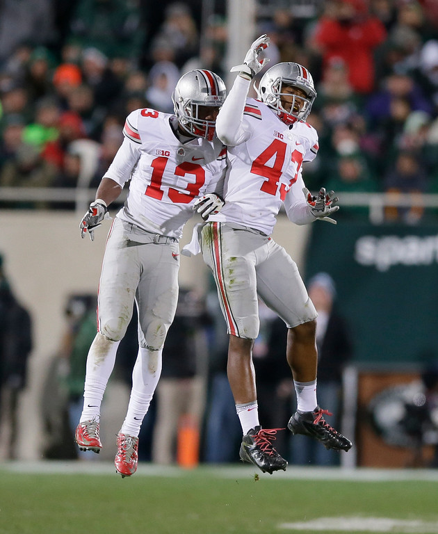 . Ohio State cornerback Eli Apple (13) and linebacker Darron Lee (43) celebrate after a play during the second half of an NCAA college football game against Michigan State in East Lansing, Mich., Saturday, Nov. 8, 2014. Ohio State won 49-37. (AP Photo/Carlos Osorio)
