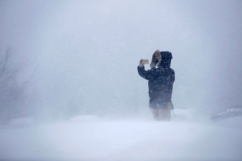 . Cassie Peterson uses a phone to record the whiteout conditions during the latest winter storm, Tuesday, March 13, 2018, in Portland, Maine. The third major nor\'easter in two weeks slammed the storm-battered Northeast Tuesday with blizzard conditions. (AP Photo/Robert F. Bukaty)