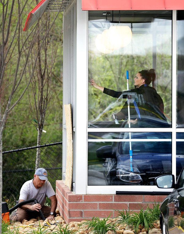 . A worker vacuums debris from shattered glass as another worker cleans windows inside a Waffle House restaurant Monday, April 23, 2018, in Nashville, Tenn. A suspect police have identified as Travis Reinking shot and killed at least four people at the Waffle House Sunday. (AP Photo/Mark Humphrey)