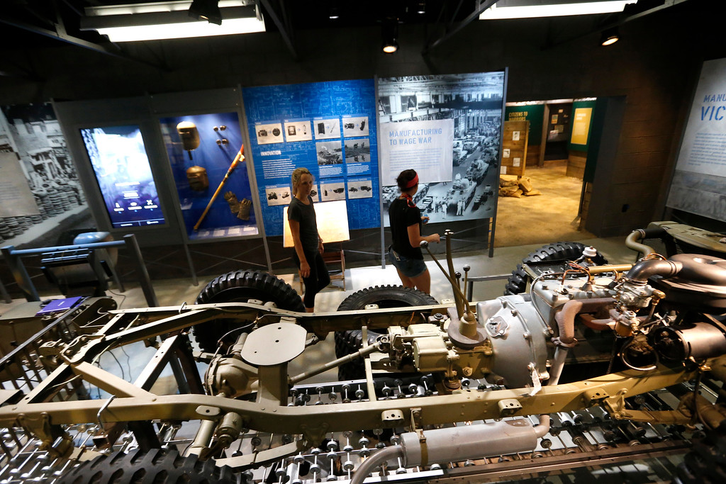 ". Workers walk past a mock-up of an assembly line manufacturing army jeeps as part of the permanent exhibit ""Salute to the Home Front\"" at the National World War II Museum which will open to the public this Saturday, in New Orleans, Monday, June 5, 2017. The exhibit tells the home front story from the 1920s to the development of the atomic bomb. (AP Photo/Gerald Herbert)"