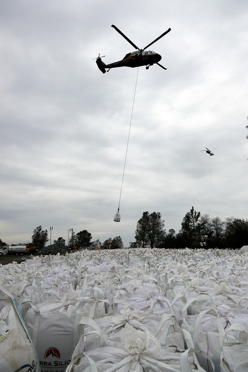 . A helicopter carries sandbags in the direction of a damaged dam Wednesday, Feb. 15, 2017, in Oroville, Calif. The Oroville Reservoir is continuing to drain Wednesday as state water officials scrambled to reduce the lake\'s level ahead of impending storms. (AP Photo/Marcio Jose Sanchez)