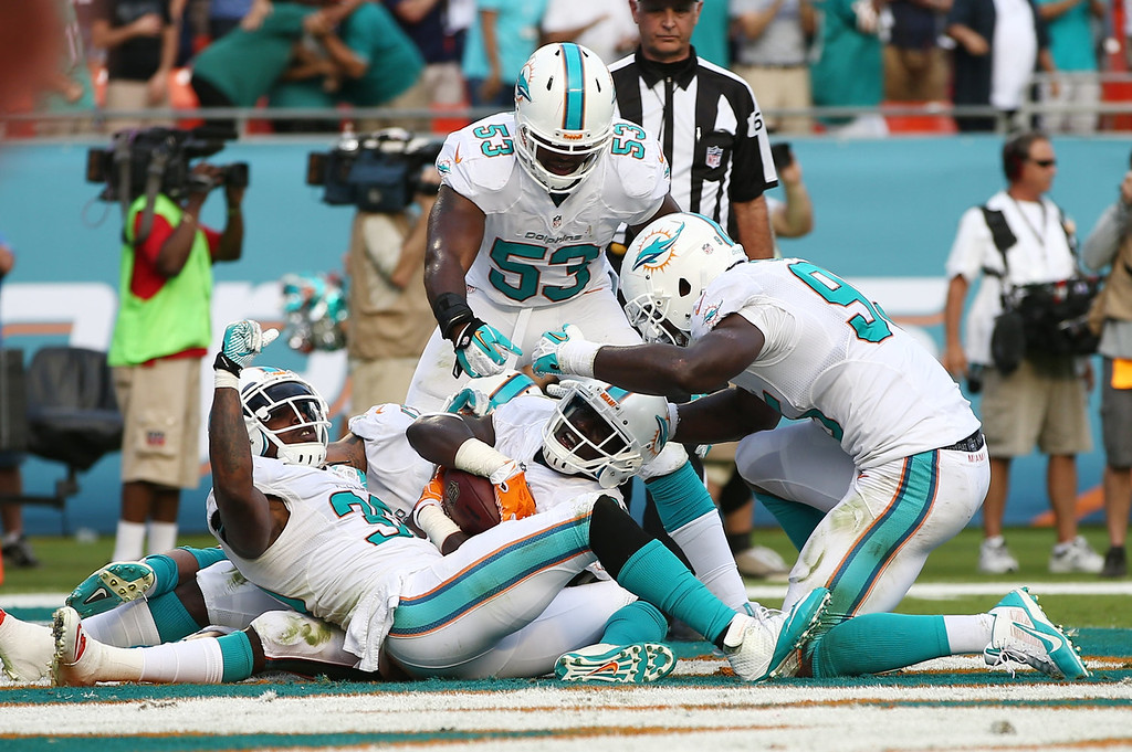 . Miami Dolphins Michael Thomas, center, is congratulated by teammates Chris Clemons (30), left, and Jelani Jenkins (53) after Thomas intercepted a pass intended for New England Patriots wide receiver Austin Collie (10) during the second half of an NFL football game, Sunday, Dec. 15, 2013, in Miami Gardens, Fla. The Dolphins defeated the Patriots 24-20. (AP Photo/J Pat Carter)