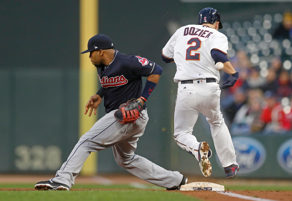 . Minnesota Twins\' Brian Dozier, right, reaches safely as Cleveland Indians\' Carlos Santana, left, misses the throw duirng the first inning of a baseball game Tuesday, April 18, 2017, in Minneapolis. (AP Photo/Jim Mone)