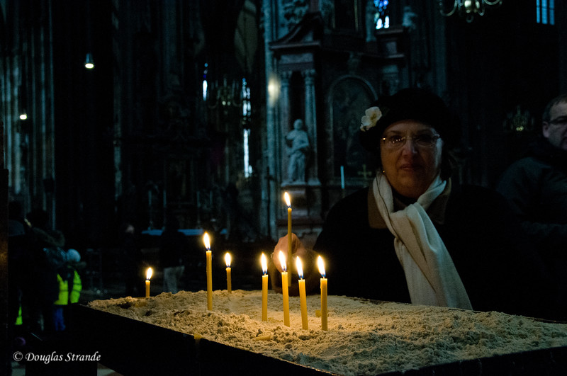 Louise lighting a candle in St. Stephen's Cathedral in Vienna