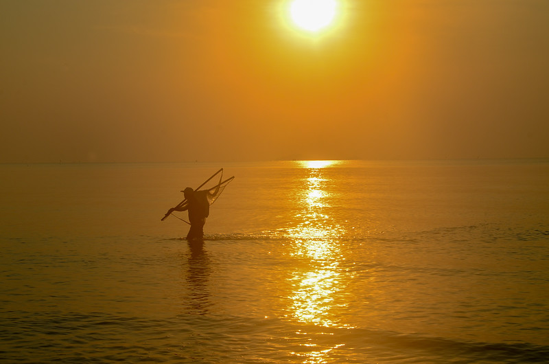 Net Fisherman ocean wading with tropical sunrise seascape , Thailand.