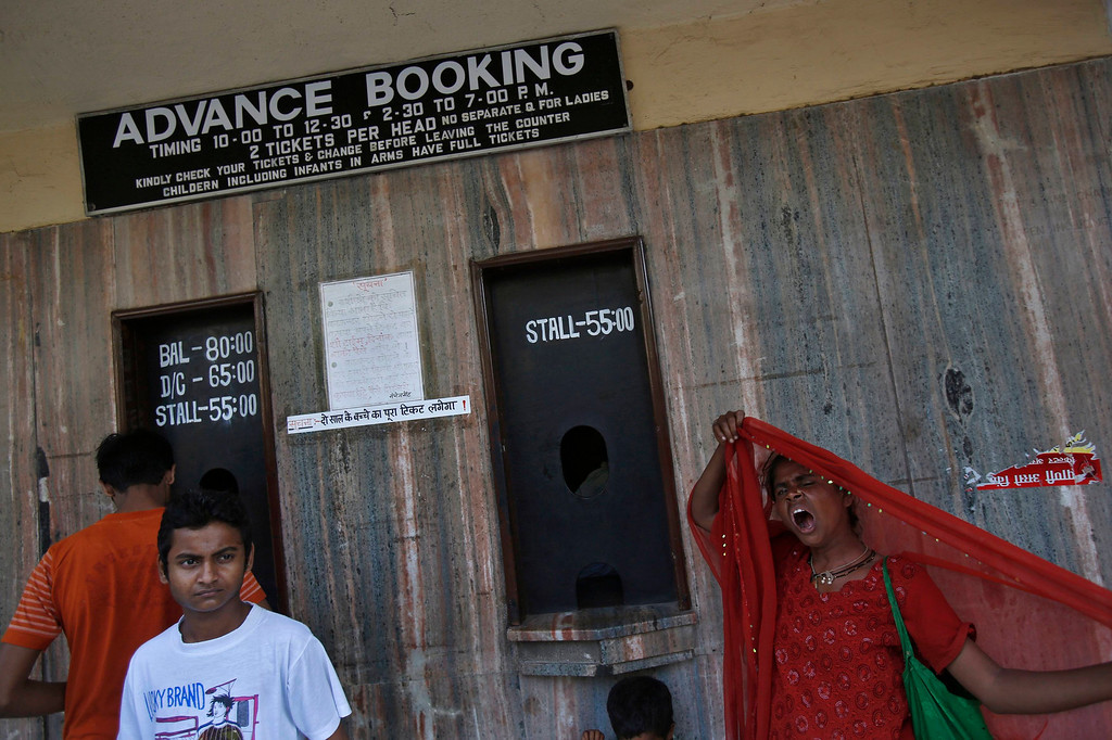 """. Patrons wait to buy tickets for a Bollywood film at a cinema in Mumbai April 14, 2013. Indian cinema marks 100 years since Dhundiraj Govind Phalke\'s black-and-white silent film \""""Raja Harishchandra\"""" (King Harishchandra) held audiences spellbound at its first public screening on May 3, 1913, in Mumbai. Indian cinema, with its subset of Bollywood for Hindi-language films, is now a billion-dollar industry that makes more than a thousand films a year in several languages. It is worth 112.4 billion rupees (over $2 billion) and leads the world in terms of films produced and tickets sold. Picture taken April 14, 2013. REUTERS/Vivek Prakash"""