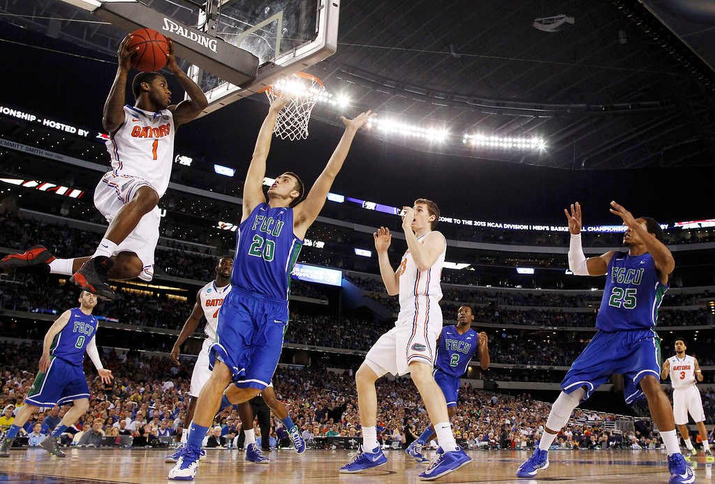 . Florida Gators guard Kenny Boynton (L) passes while being guarded by Florida Gulf Coast Eagles forward Chase Fieler during the first half in their South Regional NCAA men\'s basketball game in Arlington, Texas March 29, 2013. REUTERS/Jim Young