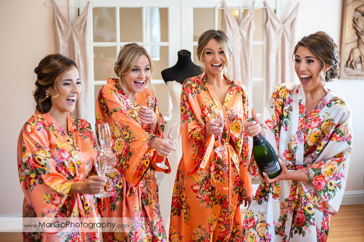 bride and bridesmaids in flower robes opening champagne bottle during getting ready in Walnut Creek