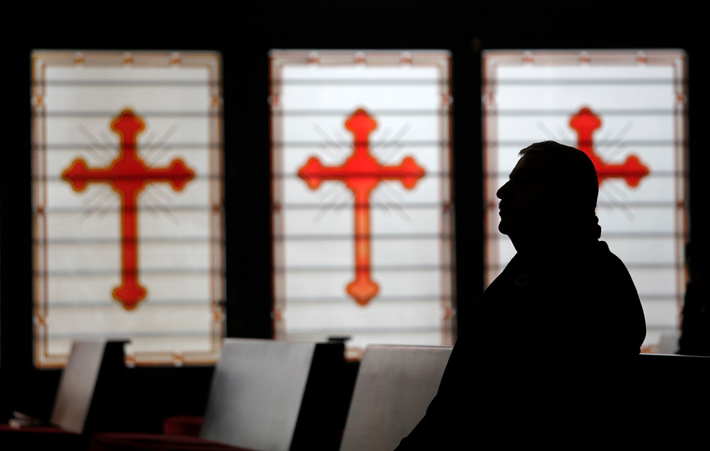 . An Iraqi Orthodox Christian refugee attends a morning Christmas mass at the Saint Afram Syrian Orthodox Church in Amman, Jordan, Wednesday, Dec. 25, 2013. Syrian and Iraqi Orthodox Christian families attended morning mass of Christmas and pray for peace in their countries. (AP Photo/Mohammad Hannon)