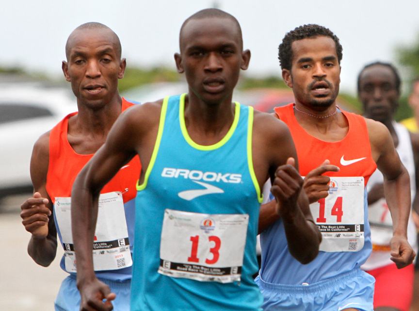 . Shadrack Kosgei, left and Aschalew Meketa Neguse, right, trail behind first place winner Nelson Oyugi during the 2013 Wharf to Wharf race on Sunday. (Kevin Johnson/Sentinel)
