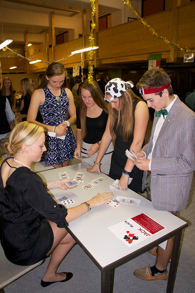 Ms. Geringer dealing out cards to Grace, Mady, Ema, and Brett during Casino Night