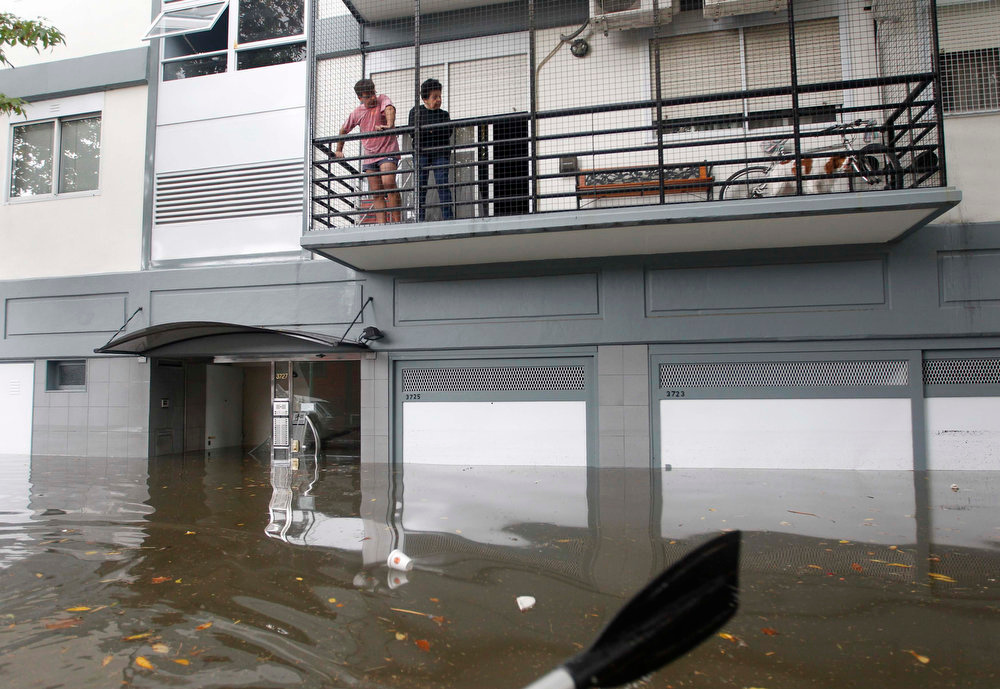 . Residents look down from a balcony at a flooded street after a rainstorm in Buenos Aires April 2, 2013. Thunderstorms damaged property and vehicles, cut power and caused delays on flights in Buenos Aires and its suburbs. The City\'s SAME emergency service announced that the death toll has risen to five.   REUTERS/Enrique Marcarian