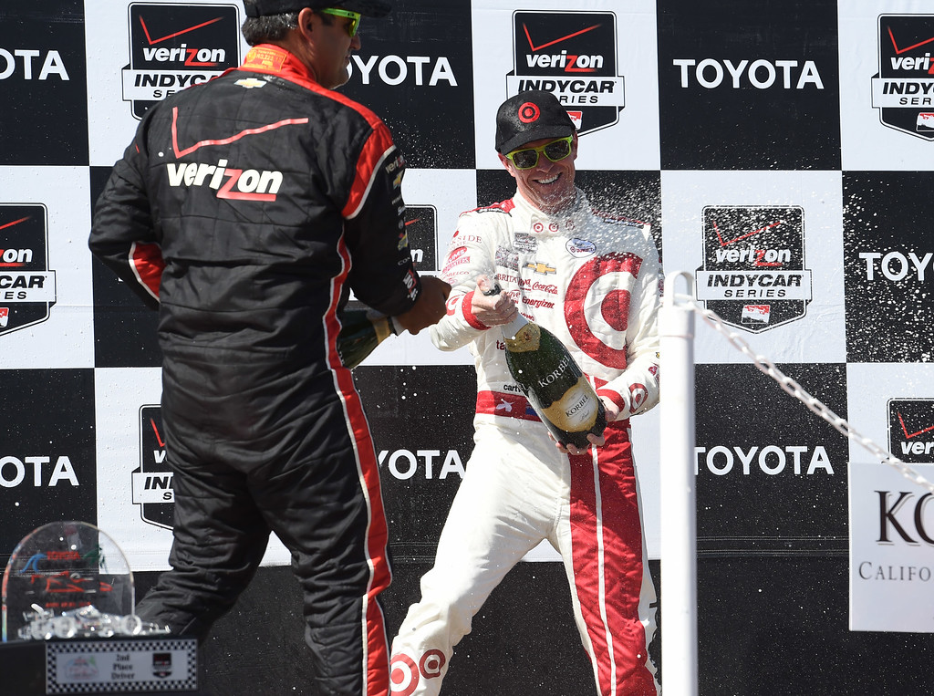 . Toyota Grand Prix of Long Beach winner Scott Dixon, right, sprays champagne on 3rd place finisher, Juan Pablo Montoya,left, on the winners podium.  Long Beach  Calif., Sunday,  April,19, 2015.     (Photo by Stephen Carr / Daily Breeze)