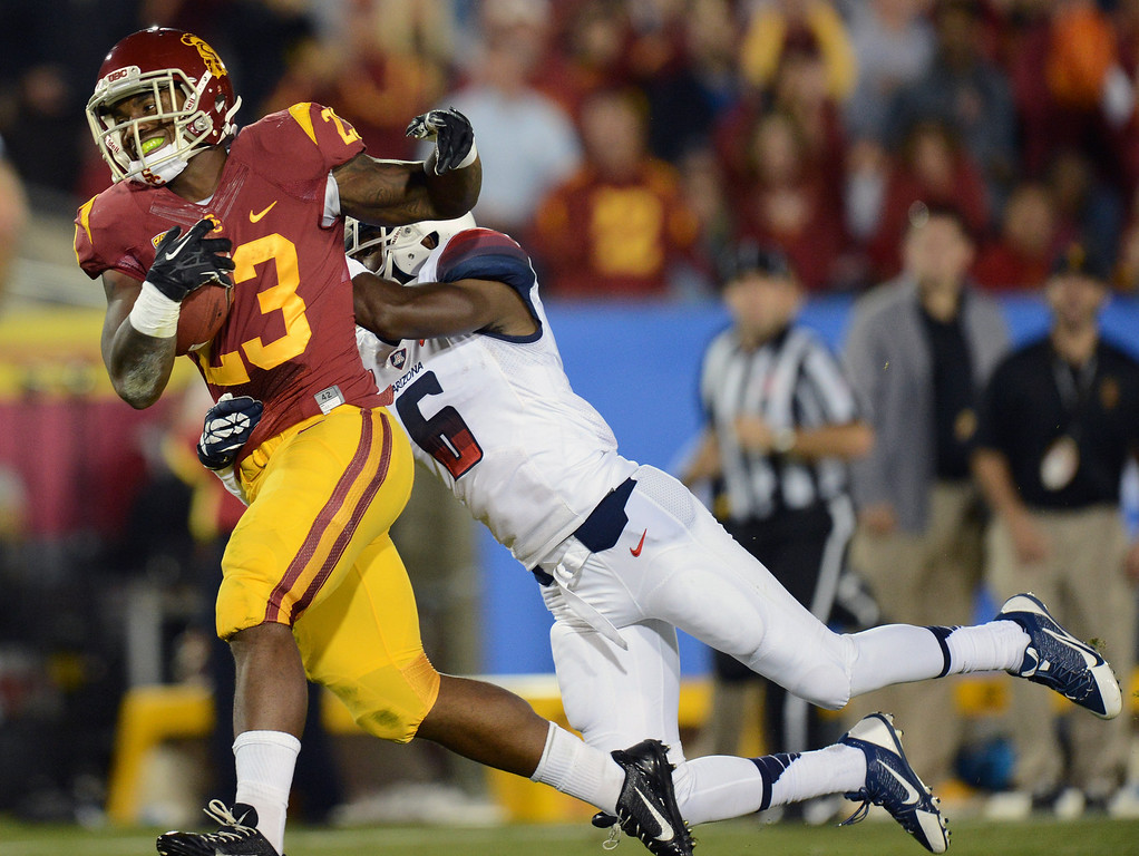 . USC\'s  Tre Madden #23 escapes the tackle of Arizona\'s Josh Shaw #6 to score a touchdown during their game at the Los Angeles Memorial Coliseum Thursday, October 10, 2013. (Photo by Hans Gutknecht/Los Angeles Daily News)