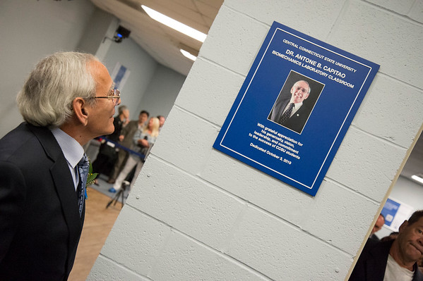 10/03/19 Wesley Bunnell | StaffrrCCSU officially opened the Dr. Antone B. Capitao Biomechanics Laboratory Classroom with a ribbon cutting on Thursday October 3, 2019. Dr. Capitao looks up at the plaque dedicated in his honor.