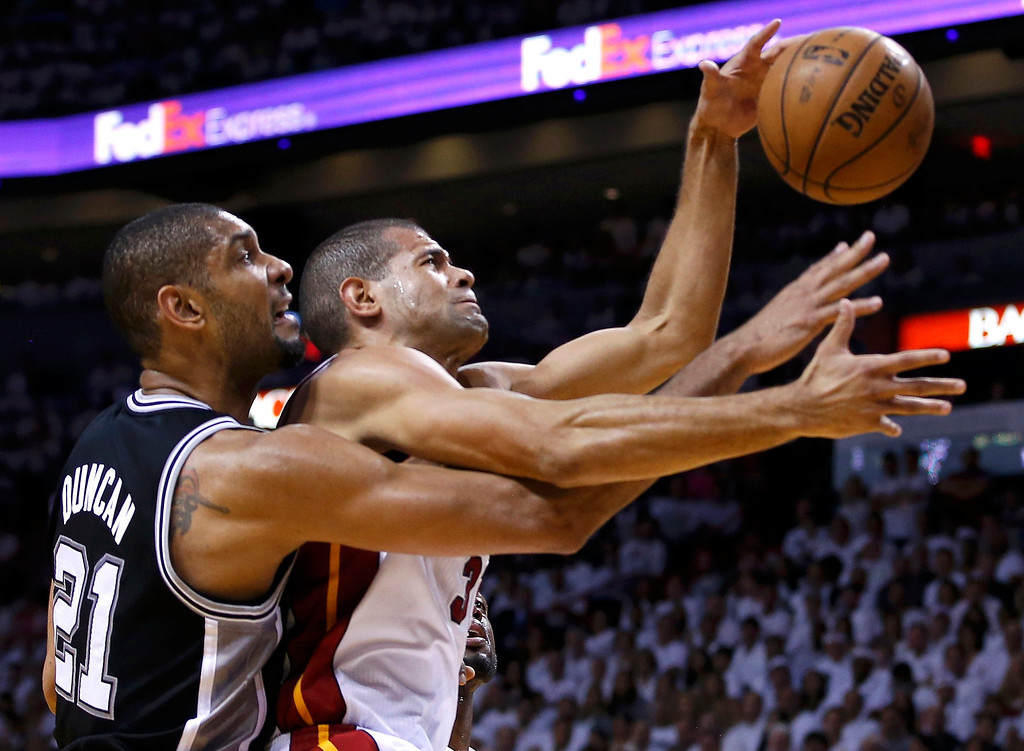 . San Antonio Spurs\' Tim Duncan (L) tangles with Miami Heat\'s Shane Battier during the second quarter in Game 7 of their NBA Finals basketball playoff in Miami, Florida June 20, 2013. REUTERS/Mike Segar