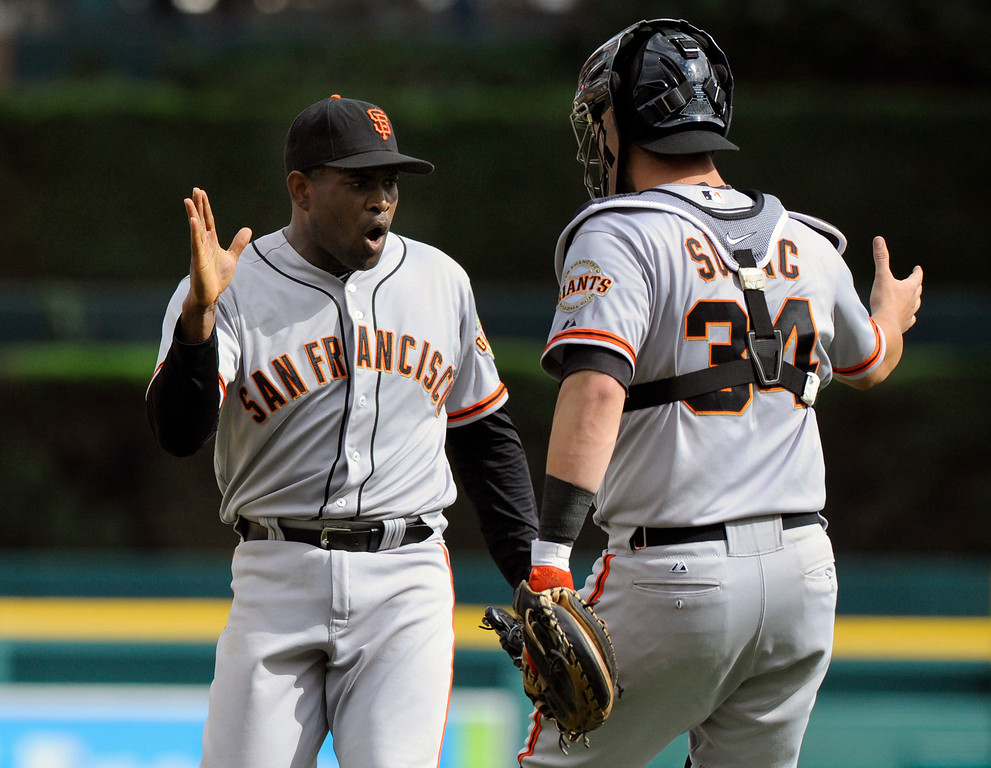 . San Francisco Giants pitcher Santiago Casilla, left, celebrates with teammate Andrew Susac after the final out of the baseball game against the Detroit Tigers Saturday, Sept. 6, 2014, in Detroit, Mich.  The Giants won 5-4.  (AP Photo/Jose Juarez)
