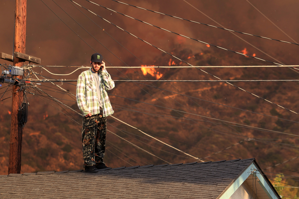 . A resident on the roof of a house talks on the phone as a wildfire burns in the hills just north of the San Gabriel Valley community of Glendora, Calif. on Thursday, Jan 16, 2014. Southern California authorities have ordered the evacuation of homes at the edge of a fast-moving wildfire burning in the dangerously dry foothills of the San Gabriel Mountains. (AP Photo/Ringo H.W. Chiu)