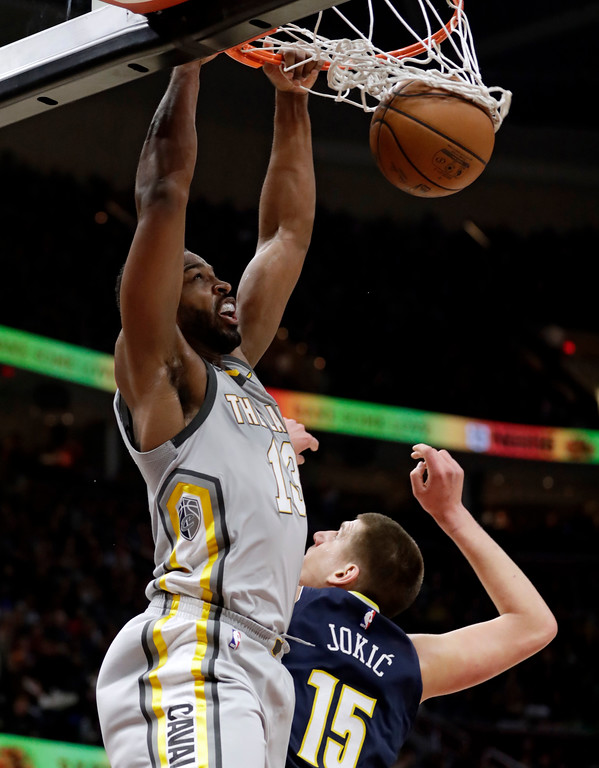 . Cleveland Cavaliers\' Tristan Thompson, left, dunks the ball against Denver Nuggets\' Nikola Jokic (15), from Serbia, in the first half of an NBA basketball game, Saturday, March 3, 2018, in Cleveland. (AP Photo/Tony Dejak)