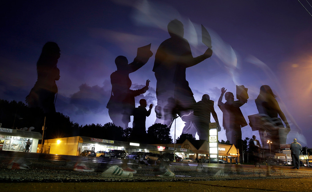 . Protesters march in the street as lightning flashes in the distance in Ferguson, Mo. on Wednesday, Aug. 20, 2014. On Aug. 9, 2014, a white police officer fatally shot Michael Brown, an unarmed black 18-year old, in the St. Louis suburb. (AP Photo/Jeff Roberson, File)