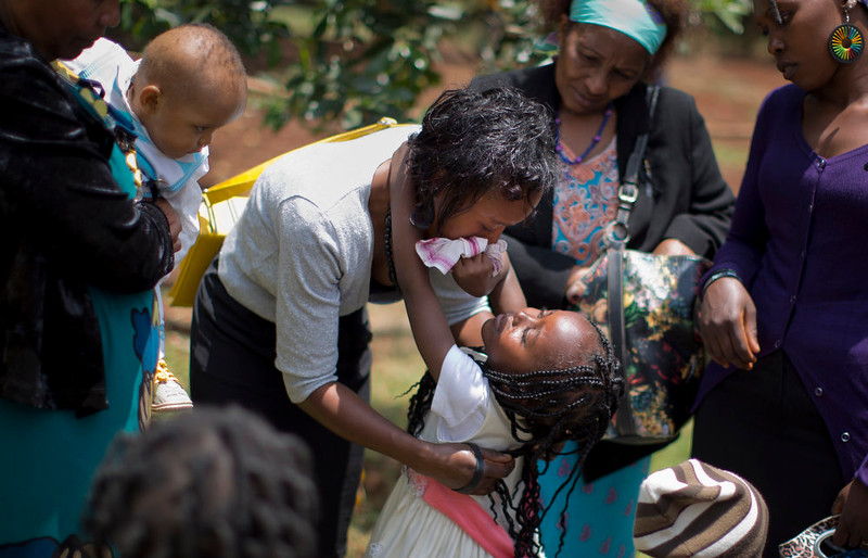 . Gloria, 4, center, whose father Christopher Chewa was killed in the Westgate Mall attack, wipes the tears from the eyes of her mother Faith Njoki as they hug, while her brother Edwin, 1, left is held by a relative, after joining other families of the victims to lay flowers and remember at the Amani Garden memorial site in the Karura Forest in Nairobi, Kenya Sunday, Sept. 21, 2014. Kenya is marking one year since four gunmen stormed the upscale Westgate Mall in Nairobi, killing 67 people, and a memorial plaque with the names of the victims was unveiled at the popular forest on the edge of the city. (AP Photo/Ben Curtis)