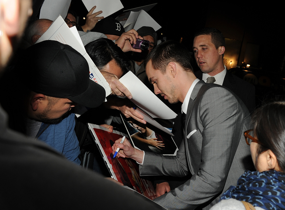 "Description of . Actor Nicholas Hoult signs autographs as he arrives for the Los Angeles premiere of Summit Entertainment\'s ""Warm Bodies\"" at ArcLight Cinemas Cinerama Dome on January 29, 2013 in Hollywood, California.  (Photo by Kevin Winter/Getty Images)"