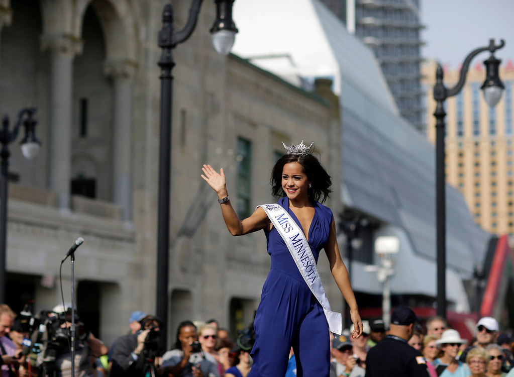 . Miss Minnesota Rebecca Yeh waves as she walks on a runway as Miss America contestants arrive in Atlantic City, N.J. on Tuesday, Sept. 3, 2013. The Miss America pageant is back in the city where it began, six years after spurning the city for Las Vegas. The pageant held a welcoming ceremony Tuesday for the 53 contestants, one from each state plus the District of Columbia, Puerto Rico and the U.S. Virgin n Islands. The contestants filed out of Boardwalk Hall, where the competition will begin next week and culminate days later, and walked across the Boardwalk to a stage. (AP Photo/Mel Evans)