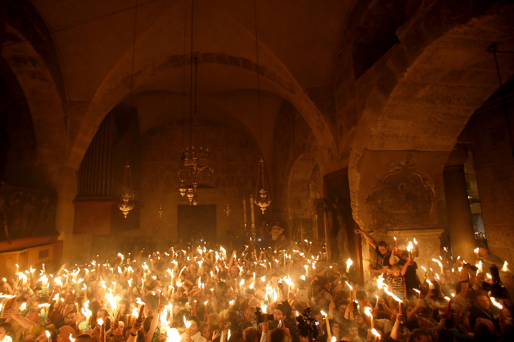 """. Christian Orthodox worshippers hold up candles lit from the \""""Holy Fire\"""" as thousands gather in the Church of the Holy Sepulchre in Jerusalem\'s old city on April 19, 2014 during the \""""Holy Fire\"""" ceremony on the eve of the Orthodox Easter.  AFP PHOTO/GALI TIBBON/AFP/Getty Images"""