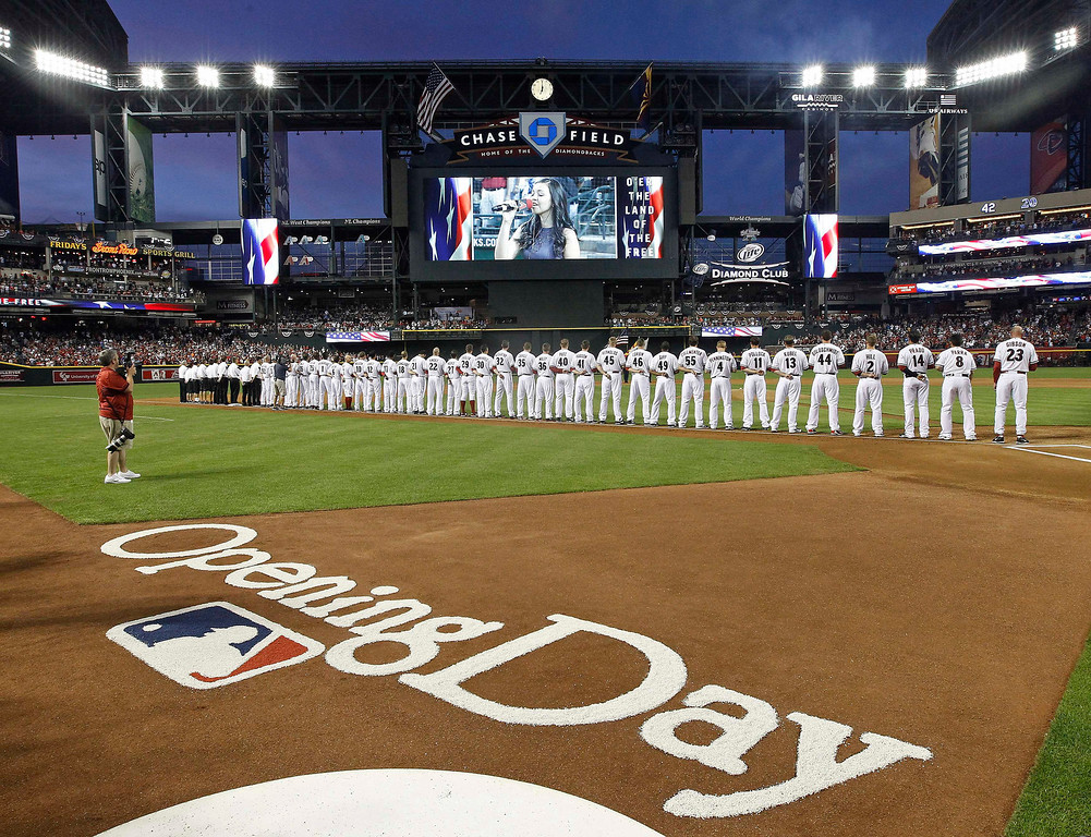 . Arizona Diamondbacks players stand along the third base line during Opening Day festivities before the start of their MLB National League baseball game against the St. Louis Cardinals in Phoenix, Arizona, April 1, 2013. REUTERS/Ralph D. Freso