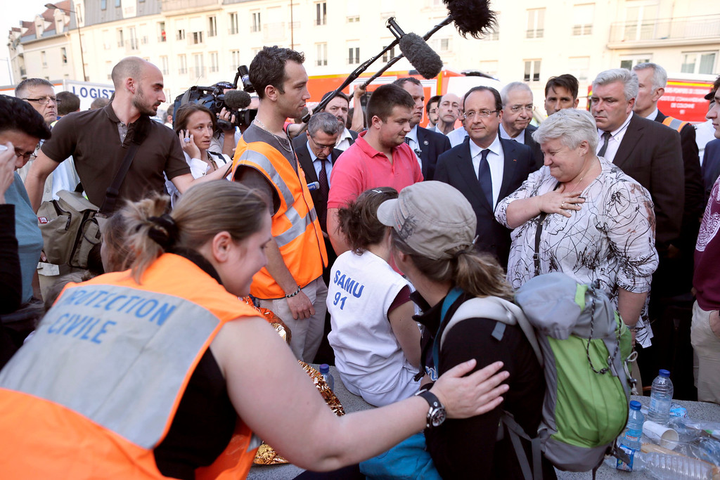. French President Francois Hollande (3rdR) is surrounded by victims and rescue workers during a visit on the site of an intercity train accident at the Bretigny-sur-Orge train station near Paris July 12, 2013. REUTERS/Kenzo Tribouillard/Pool