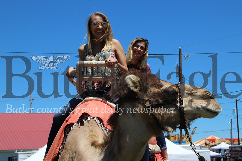 Haley Damico (front), 18, of Pittsburgh and Debbie Paginski, 18, of O'Hara Township, ride a camel during the Big Butler Fair on July 7, 2018.