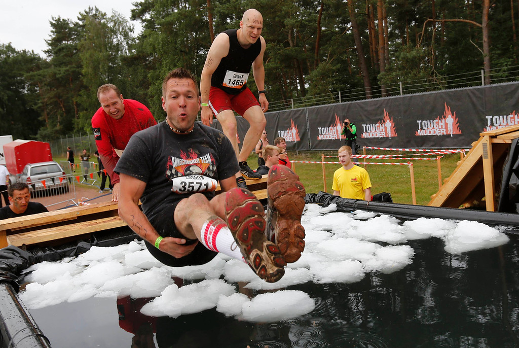 ". A participant of ""Tough Mudder\"" endurance event series jumps into a tub filled with ice-cubes at the \""Arctic Enema\"" obstacle in the Fursten Forest, a former British Army training ground near the north-western German city of Osnabrueck July 13, 2013. The hardcore but un-timed event over 16 km (10 miles) was designed by British Special Forces to test mental as well as physical strength. Some 4,000 competitors had to overcome obstacles of common human fears, such as fire, water, electricity and heights.   REUTERS/Wolfgang Rattay"