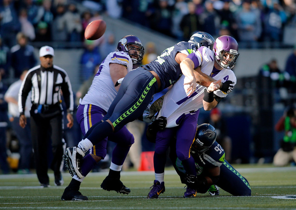. Minnesota Vikings quarterback Christian Ponder, right, is hit by Seattle Seahawks\' Michael Bennett, second from left, and Brandon Mebane (92), right, as he attempts a pass in the first half of an NFL football game Sunday, Nov. 17, 2013, in Seattle. The Seahawks won 41-20. (AP Photo/John Froschauer)