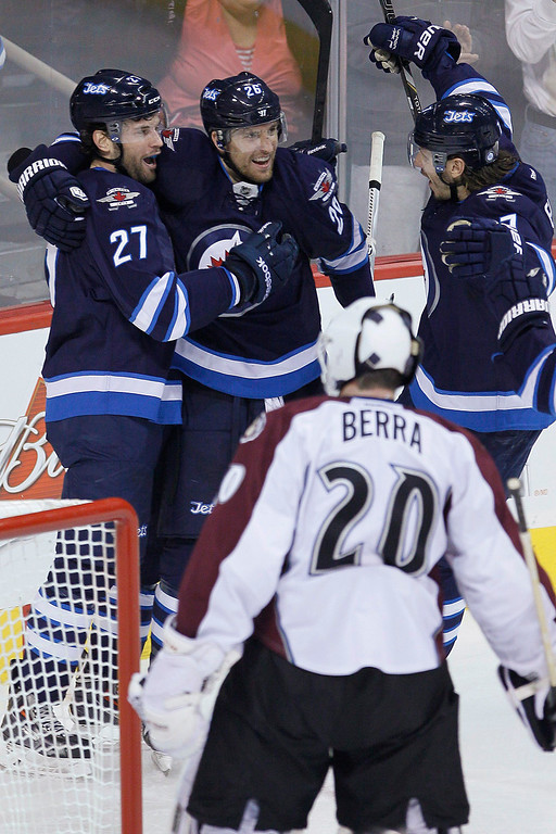 . Winnipeg Jets\' Eric Tangradi (27), Blake Wheeler (26) and Keaton Ellerby celebrate Tangradi\'s goal against Colorado Avalanche goaltender Reto Berra (20) during the first period of an NHL hockey game Wednesday, March 19, 2014, in Winnipeg, Manitoba. (AP Photo/The Canadian Press, John Woods)