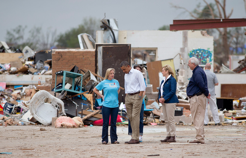 . President Barack Obama listens to Plaza Towers Elementary School principal Amy Simpson, left, with Oklahoma Gov. Mary Fallin, second from right, and FEMA administrator W. Craig Fugate, right as he views the devastation of the Plaza Towers Elementary School, Sunday, May 26, 2013, in Moore, Okla., after the massive tornado and severe weather the we before.  (AP Photo/Carolyn Kaster)