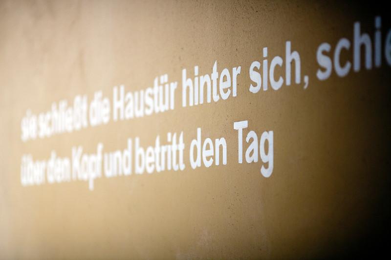 Message on a wall: Sie schließt die Haustür hinter sich schiebt die Kapuze über den Kopf und betritt den Tag, Berlin, Germany.