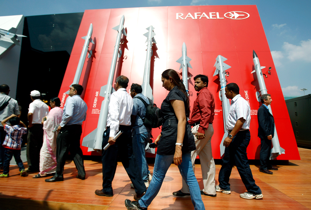 Description of . Visitors walk past a display of missiles by Israel's Rafael Advanced Defense Systems Ltd. on the second day of the Aero India 2013 at Yelahanka air base in Bangalore, India, Thursday, Feb. 7, 2013. More than 600 aviation companies along with delegations from 78 countries are participating in the five-day event that started Wednesday. (AP Photo/Aijaz Rahi)