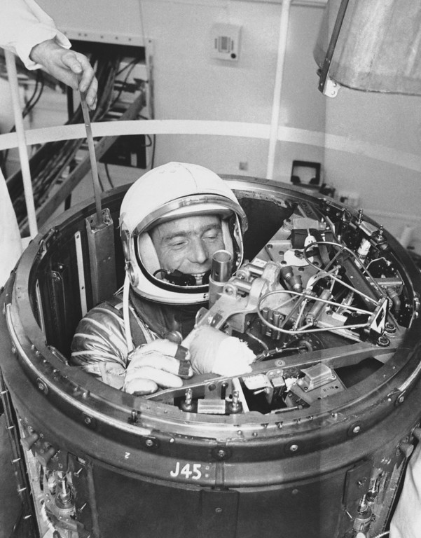 . Mercury Astronaut M. Scott Carpenter checks out method of escape through top of spacecraft he will ride on three orbits of the earth after launch at Cape Canaveral on Thursday, May 17. The practice is held in the training room at Hanger S at the Cape Canaveral, May 10, 1962. (AP Photo)