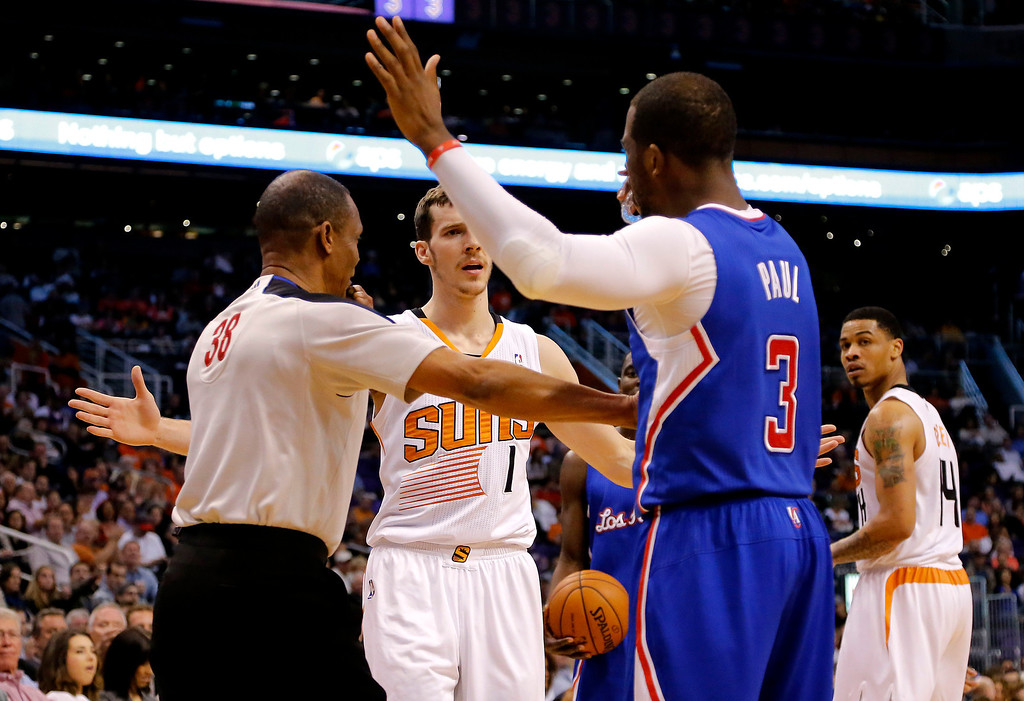 . Referee Michael Smith (38) separates Phoenix Suns guard Goran Dragic (1), of Slovenia, and Los Angeles Clippers guard Chris Paul (3) during the first half of an NBA basketball game, Wednesday, April 2, 2014, in Phoenix. Paul was called for a technical foul for interfering with Dragic. (AP Photo/Matt York)
